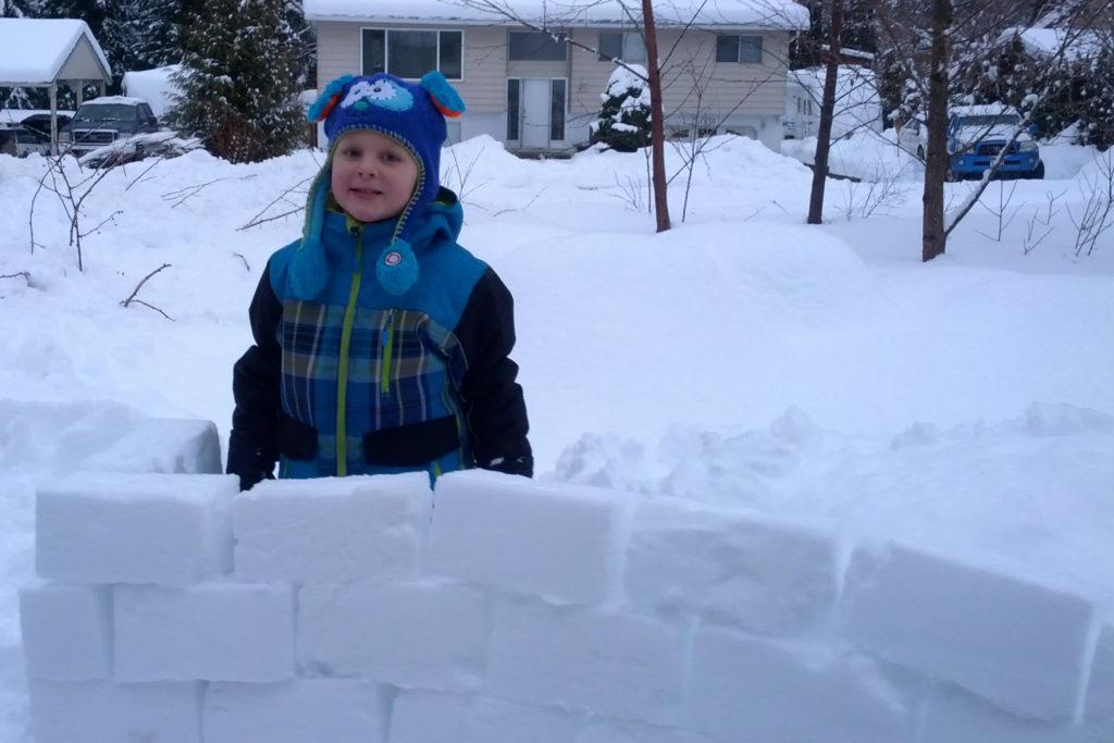 Kiddo behind a snow-brick wall
